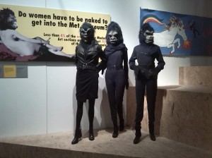 Visual installation of the Guerrilla Girls masks and banner poster